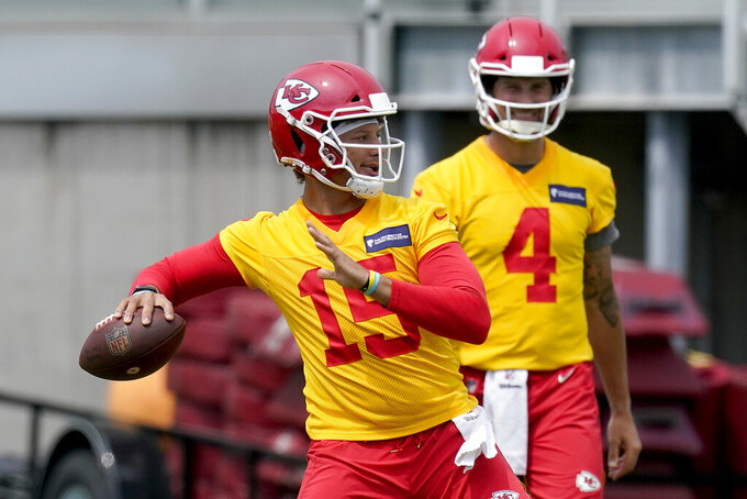 Kansas City Chiefs quarterback Patrick Mahomes (15) throws while teammate Chad Henne waits his turn during the NFL football team's minicamp Wednesday, June 16, 2021, in Kansas City, Mo. (AP Photo/Charlie Riedel)