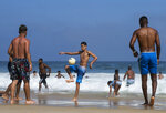 Beachgoers play with a soccer ball along the shore of Ipanema Beach amid the new coronavirus pandemic in Rio de Janeiro, Brazil, Sunday, Sept.6, 2020. Brazilians are packing the beaches and bars this weekend, taking advantage of a long holiday to indulge in normal life even as the COVID-19 pandemic rages on. (AP Photo/Bruna Prado)