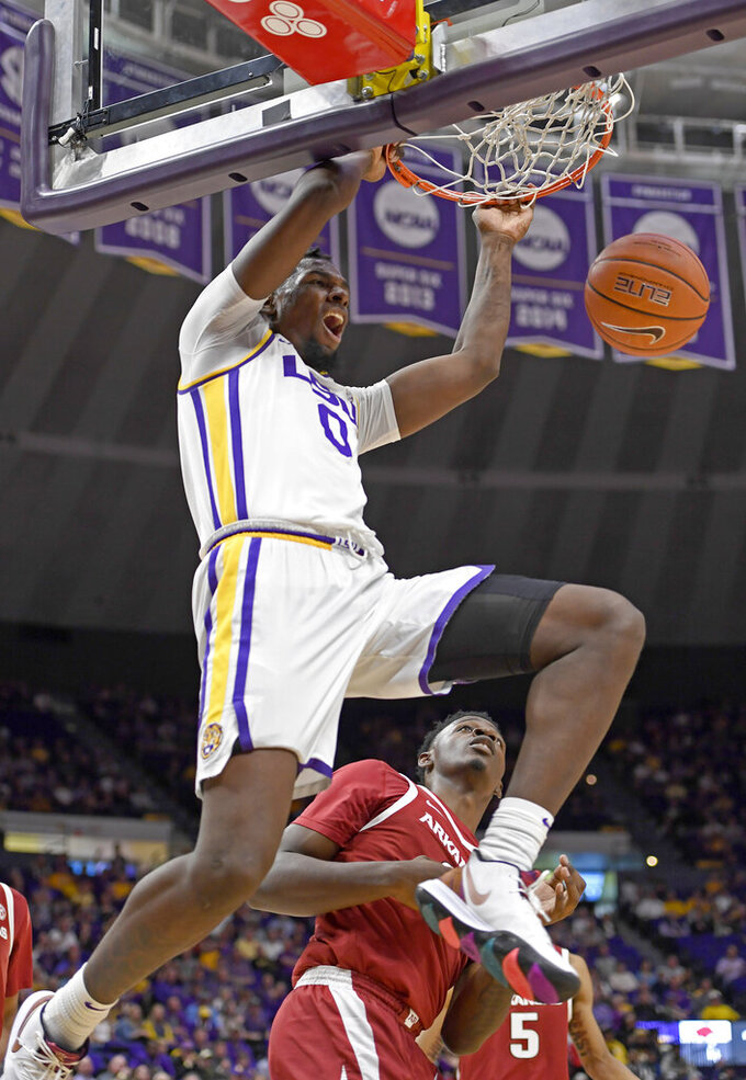 LSU forward Naz Reid (0) dunks in front of Arkansas forward Adrio Bailey (2) during the first half of an NCAA college basketball game Saturday, Feb. 2, 2019, in Baton Rouge, La. (AP Photo/Bill Feig)
