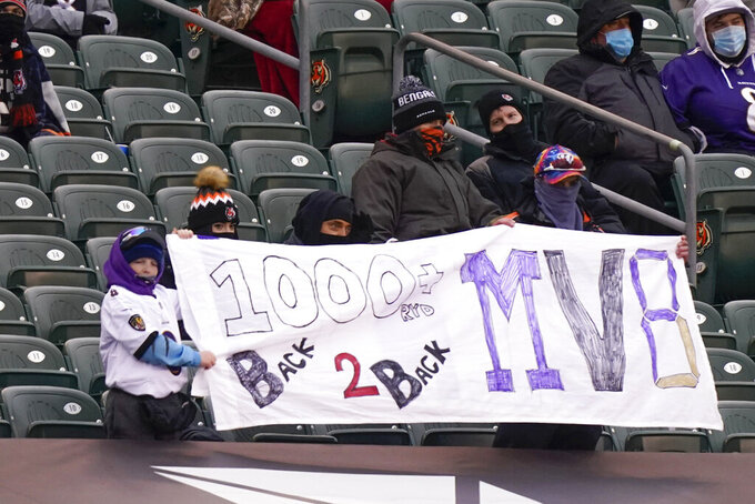 Some Baltimore Ravens fans hold up a sign supporting Baltimore Ravens quarterback Lamar Jackson (8) for most valuable player honors while attending an NFL football game between the Cincinnati Bengals and the Baltimore Ravens, Sunday, Jan. 3, 2021, in Cincinnati. (AP Photo/Bryan Woolston)