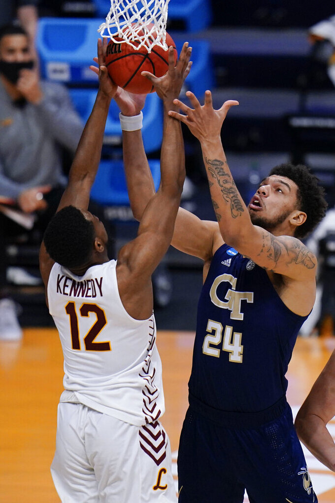 Georgia Tech forward Rodney Howard (24) goes for a rebound against Loyola Chicago guard Marquise Kennedy (12) in the first half of a college basketball game in the first round of the NCAA tournament at Hinkle Fieldhouse, Indianapolis, Friday, March 19, 2021. (AP Photo/AJ Mast)