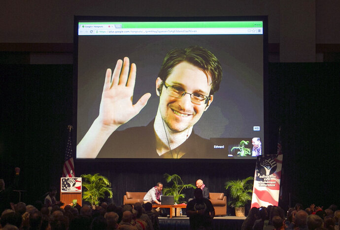 FILE - In this Feb. 14, 2015, file photo, Edward Snowden appears on a live video feed broadcast from Moscow at an event sponsored by ACLU Hawaii in Honolulu. Snowden has written a memoir, telling his life story in detail for the first time and explaining why he chose to risk his freedom to become perhaps the most famous whistleblower of all time. (AP Photo/Marco Garcia, File)