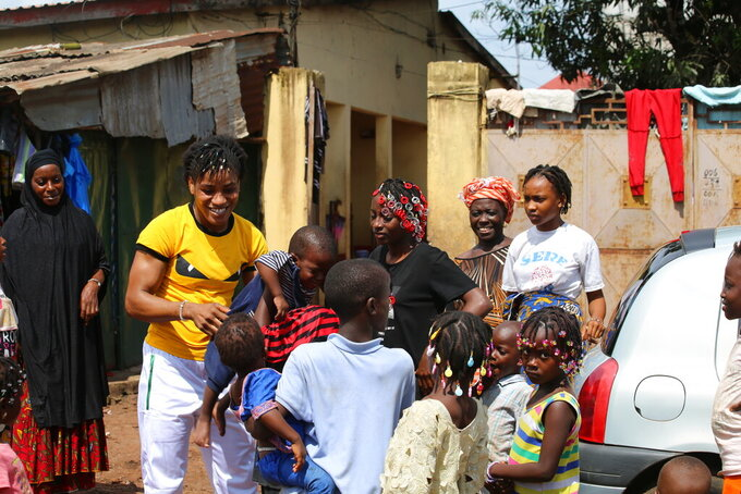 Guinean wrestler Fatoumata Yarie Camara is welcomed by family members as she arrives at her house in Conakry, Guinea, Monday July 19, 2021. A West African wrestler's dream of competing in the Olympics has come down to a plane ticket. Fatoumata Yarie Camara is the only Guinean athlete to qualify for these Games. She was ready for Tokyo, but confusion over travel reigned for weeks. The 25-year-old and her family can't afford it. Guinean officials promised a ticket, but at the last minute announced a withdrawal from the Olympics over COVID-19 concerns. Under international pressure, Guinea reversed its decision. (AP Photo/Youssouf Bah)