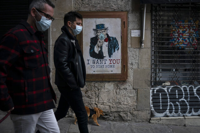 People walk past a poster that reads 'I want you to stay home', by artist TvBoy amid a lockdown in Barcelona, Spain, Tuesday, March 24, 2020. More than 1.5 billion around the world have been told to stay in their homes. For most people, the new coronavirus causes only mild or moderate symptoms. For some it can cause a more serious illness. (AP Photo/Felipe Dana)
