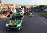 Iraqi security forces raise Iraqi national flags in a parade marking the year anniversary of the defeat of the Islamic State group in Iraq in Tahrir Square, in central Baghdad, Monday, Dec. 10, 2018. Iraq celebrated the anniversary of its costly victory over the Islamic State group, which has lost virtually all the territory it once held but still carries out sporadic attacks. (AP Photo/Ali Abdul Hassan)