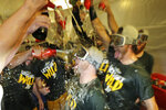 Oakland Athletics players dump beer in the clubhouse as the celebrate after a baseball game against the Seattle Mariners, Friday, Sept. 27, 2019, in Seattle. The Athletics lost 4-3 to the Mariners, but clinched a wild-card berth in the American League before the first pitch of the game when the Cleveland Indians lost to the Washington Nationals. (AP Photo/Ted S. Warren)