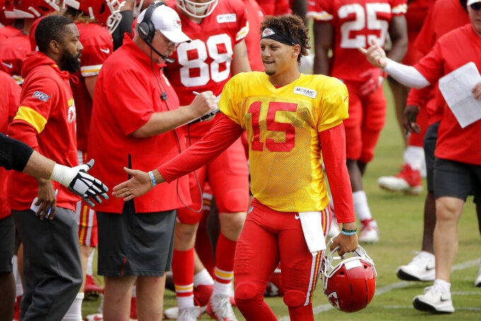 FILE - In this Aug. 2, 2019, file photo, Kansas City Chiefs quarterback Patrick Mahomes greets a teammate during NFL football training camp in St. Joseph, Mo. Mahomes has just about everyone in his supporting cast back this season, losing only wide receiver Chris Conley and getting second-round pick Mecole Hardman was a replacement. In other words, Mahomes could very well surpass the eye-popping numbers he put up last season. (AP Photo/Charlie Riedel, File)