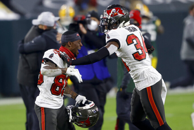 Tampa Bay Buccaneers' Javon Hagan and Jaydon Mickens, left, celebrate after winning the NFC championship NFL football game against the Green Bay Packers in Green Bay, Wis., Sunday, Jan. 24, 2021. The Buccaneers defeated the Packers 31-26 to advance to the Super Bowl. (AP Photo/Jeffrey Phelps)