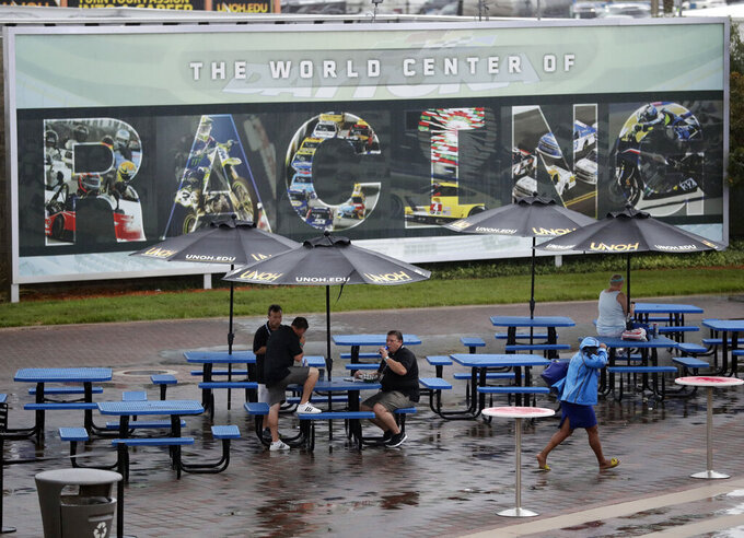 Race fans take cover under umbrellas in the Fan Zone area in the infield during a rain storm before the NASCAR Xfinity Series auto race at Daytona International Speedway, Friday, July 5, 2019, in Daytona Beach, Fla. (AP Photo/John Raoux)