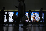 Commuters walk by a computer and mobile phone's RPG games advertisement at a subway station in Beijing Tuesday, Sept. 14, 2021. China has set new rules limiting the amount of time kids can spend playing online games. (AP Photo/Andy Wong)