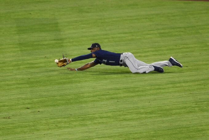 Seattle Mariners center fielder Kyle Lewis dives to catch a ball hit for a sacrifice fly by Los Angeles Angels' Justin Upton during the sixth inning of a baseball game in Anaheim, Calif., Tuesday, July 28, 2020. (AP Photo/Kelvin Kuo)