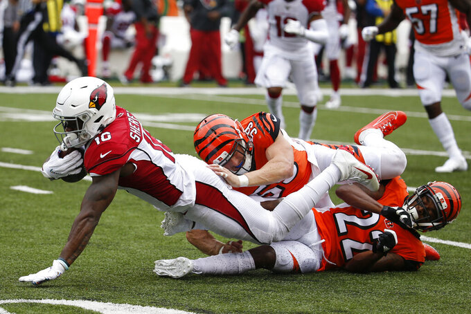 Arizona Cardinals wide receiver Trent Sherfield, left, is tackled by Cincinnati Bengals outside linebacker Nick Vigil (59) and cornerback William Jackson (22) in the first half of an NFL football game, Sunday, Oct. 6, 2019, in Cincinnati. (AP Photo/Frank Victores)