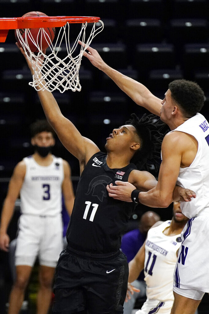 Michigan State guard A.J. Hoggard, left, drives to the basket past Northwestern forward Pete Nance during the first half of an NCAA college basketball game in Evanston, Ill., Sunday, Dec. 20, 2020. (AP Photo/Nam Y. Huh)