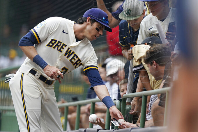 Milwaukee Brewers left fielder Christian Yelich, left, signs autographs for fans before a baseball game against the Kansas City Royals, Tuesday, July 20, 2021, in Milwaukee. (AP Photo/Nam Y. Huh)