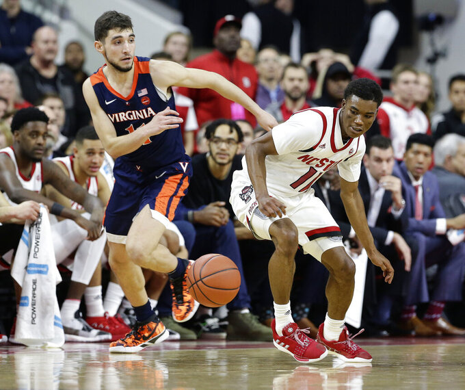 Virginia's Ty Jerome and North Carolina State's Markell Johnson (11) chase the ball during overtime in an NCAA college basketball game in Raleigh, N.C., Tuesday, Jan. 29, 2019. Virginia won 66-65. (AP Photo/Gerry Broome)