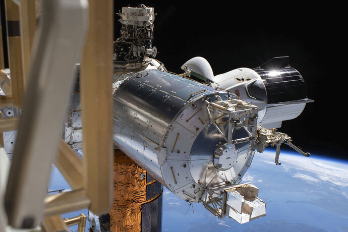 This July 1, 2020 photo made available by NASA shows the SpaceX Crew Dragon, right, docked to the International Space station, during a spacewalk conducted by astronauts Bob Behnken and Chris Cassidy. On Wednesday, July 29, 2020, SpaceX and NASA cleared the Dragon crew capsule to depart the International Space Station and head home after a two-month flight. (NASA via AP)