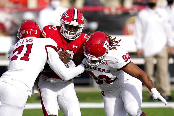 Maryland quarterback Lance LeGendre (12) is sacked by Rutgers defensive linemen Aaron Lewis (71) and Mayan Ahanotu (92) during the first half of an NCAA college football game, Saturday, Dec. 12, 2020, in College Park, Md. (AP Photo/Julio Cortez)