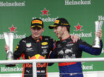 First place Red Bull driver Max Verstappen, of the Netherlands, left, and Second place finisher Toro Rosso driver Pierre Gasly, of France, celebrate on the podium after the Brazilian Formula One Grand Prix at the Interlagos race track in Sao Paulo, Brazil, Sunday, Nov. 17, 2019. (AP Photo/Silvia Izquierdo)