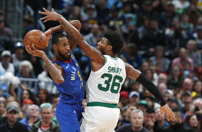 Denver Nuggets guard Will Barton, left, looks to pass the ball as Boston Celtics guard Marcus Smart defends during the second half of an NBA basketball game Friday, Nov. 22, 2019, in Denver. The Nuggets won 96-92. (AP Photo/David Zalubowski)