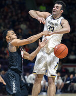 Virginia Tech guard Justin Robinson (5) and Notre Dame forward John Mooney (33) battle for a loose ball during the first half of an NCAA college basketball game Tuesday, Jan. 1, 2019, in Blacksburg, Va. (AP Photo/Don Petersen)