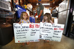 In this Friday, May 29, 2020 photo, Cora Pray, left, and her sister, Pearl Pray, hold homemade signs advertising their father's new business of selling his lobsters from his home garage in Portland, Maine. Eric Pray, background, is one of many fishermen and farmers who have pivoted quickly to sell to directly to consumers after the coronavirus shutdown cut out usual sales options. (AP Photo/Robert F. Bukaty)
