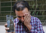 A relative weeps while showing the picture of Sohail Shahid, a Pakistani citizen who was killed in Christchurch mosque shootings, on his cell phone outside his home in Lahore, Pakistan, Sunday, March 17, 2019. Pakistan's foreign ministry spokesman says three more Pakistanis have been identified among the dead increasing the number of Pakistanis to nine killed in the mass shootings at two mosques in the New Zealand city of Christchurch. (AP Photo/K.M. Chaudary)
