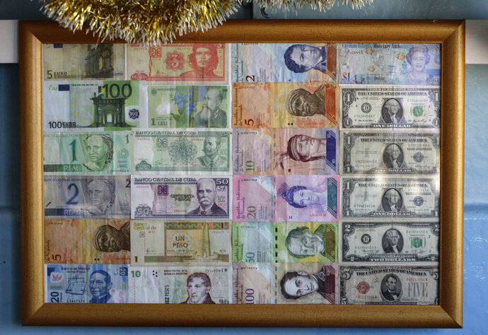 FILE - In this Dec. 19, 2014 file photo, bank notes from various countries are displayed on the wall of a small beverage shop near the beach in Havana, Cuba. Cuban officials announced Tuesday night, Oct. 15, 2019, that it will allow citizens to use 10 foreign currencies to buy products like televisions and air conditioners at state stores in an attempt to compete with a multi-billion-dollar informal market in imported goods. (AP Photo/Desmond Boylan, File)