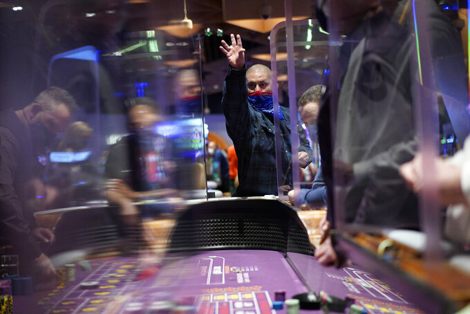 FILE - In this March 25, 2021, file photo, people play craps while wearing masks between partitions at the opening night of the Mohegan Sun Casino at Virgin Hotels Las Vegas in Las Vegas. Nevada casinos rode a robust economic rebound from coronavirus restrictions in June, taking in more than $1 billion in winnings for the fourth straight month and nearly reaching the all-time record set a month earlier, state regulators reported Thursday, July 29, 2021. (AP Photo/John Locher, File)
