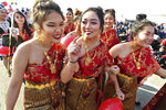 In this photo taken Dec. 26, 2017, from left front, Kathy Vang, Suleka Cha, and Der Vue, McLane High students have fun as they walk in the grand opening parade during the Hmong Cultural New Year Celebration at the fairgrounds in Fresno, Calif. The country's small Hmong American population is reeling from the shooting deaths of four men at a backyard party at a Northern California central valley city. Fresno hosts a week-long New Year's party every year that draws tens of thousands of Hmong from around the country, complete with colorful traditional dress, song, and sports games. (John Walker/The Fresno Bee via AP)
