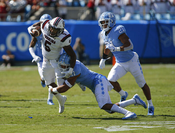 South Carolina running back Rico Dowdle, left, tries to break the tackle of North Carolina defensive back Myles Wolfolk and linebacker Chazz Surratt (21) in the first half  of an NCAA college football game in Charlotte, N.C., Saturday, Aug. 31, 2019. (AP Photo/Nell Redmond)