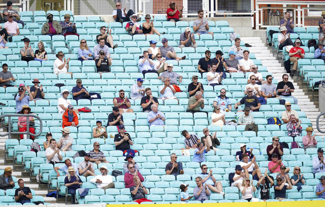 Spectators observe social distancing in the stands during the friendly cricket match at the Oval, London, Sunday, July 26, 2020. Spectators have been allowed into a sporting event in England for the first time since March when coronavirus prevention measures were tested at a cricket match between Surrey and Middlesex at The Oval ahead of a planned wider reopening of stadiums in October. Alternate rows were used across two stands and advisory signs were on show for the friendly match being watched by 1,000 people. (John Walton/PA via AP)
