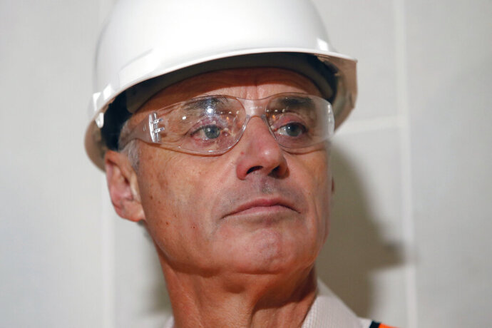 Baseball Commissioner Rob Manfred listens to a question during a tour of the under construction new Texas Rangers stadium in Arlington, Texas, Tuesday, Nov. 19, 2019. Manfred hopes the investigation into sign stealing by the Houston Astros will be completed by next season and says he has broad authority to impose discipline beyond fines, the loss of amateur draft picks and taking away international signing bonus pool allocation. (AP Photo/LM Otero)