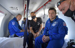 NASA astronauts Douglas Hurley, left, and Robert Behnken prepare to depart their helicopter at Naval Air Station Pensacola after the duo landed in their SpaceX Crew Dragon Endeavour spacecraft in the Gulf of Mexico off the coast of Pensacola, Fla., Sunday, Aug. 2, 2020. The Demo-2 test flight for NASA's Commercial Crew Program was the first to deliver astronauts to the International Space Station and return them safely to Earth onboard a commercially built and operated spacecraft. Behnken and Hurley returned after spending 64 days in space. (Bill Ingalls/NASA via AP)
