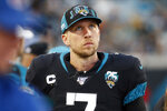 FILE - In this Dec. 8, 2019, file photo, Jacksonville Jaguars quarterback Nick Foles walks along the bench area as he looks up at the scoreboard during the first half of an NFL football game against the Los Angeles Chargers, in Jacksonville, Fla. A person familiar with the trade says the Jacksonville Jaguars have agreed to send quarterback Nick Foles to the Chicago Bears for a compensatory fourth-round draft pick. The person spoke to The Associated Press on condition of anonymity because trades don't become official until the league year begins later Wednesday, March 18, 2020. (AP Photo/Stephen B. Morton, File)