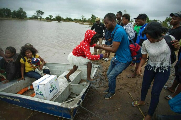 A young girl is helped from a boat after being evacuated from flood waters following cyclone force winds and heavy rain near the coastal city of Beira, Mozambique, Wednesday March 20, 2019. Torrential rains were expected to continue into Thursday and floodwaters were still rising, according to aid groups trying to get food, water and clothing to desperate survivors. It will be days before Mozambique's inundated plains drain toward the Indian Ocean and even longer before the full scale of the devastation is known. (Josh Estey/CARE via AP)