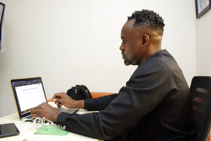 Dr. Ifeanyi Nsofor works on his laptop inside his office in Abuja, Nigeria, Monday, July 12, 2020. After Dr. Ifeanyi Nsofor and his wife were immunized with the AstraZeneca coronavirus vaccine in Nigeria, they assumed they would be free to travel this summer. They were wrong. Nsofor and his wife - and millions of others receiving vaccines through a U.N.-backed effort to distribute COVID-19 shots - are effectively banned from entering the European Union and other countries, which do not recognize the Indian-made version of the vaccine for travel. (AP Photo/ Gbemiga Olamikan)