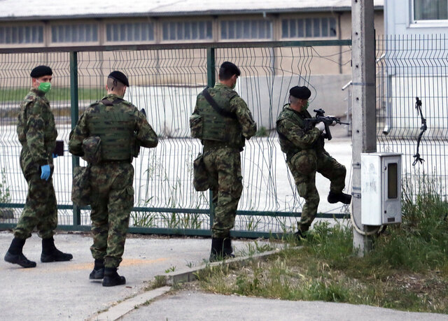 Serbian soldiers patrol around the center for refugees in Sid, about 100 km west from Belgrade, Serbia, Saturday, May 16, 2020. Serbia has sent its army to a town near the border with Croatia where hundreds of migrants remain stranded in hopes of reaching the European Union. (AP Photo/Darko Vojinovic)