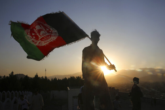 FILE - In this Aug. 19, 2019, file photo, a man waves an Afghan national flag during Independence Day celebrations in Kabul, Afghanistan. Taliban fighters attacked an army checkpoint in eastern Afghanistan, killing 14 military personnel, the Defense Ministry said Friday, May 29, 2020. (AP Photo/Rafiq Maqbool, File)