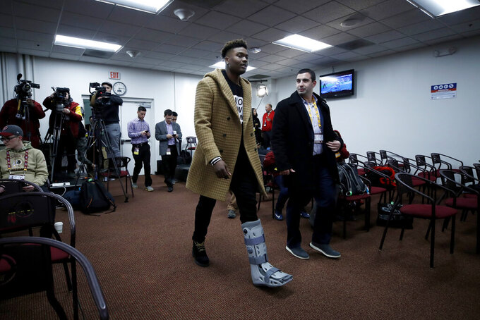 Washington Redskins quarterback Dwayne Haskins wears a boot while arriving to talk to reporters after an NFL football game against the New York Giants, Sunday, Dec. 22, 2019, in Landover, Md. The Giants won 41-35 in overtime. (AP Photo/Alex Brandon)