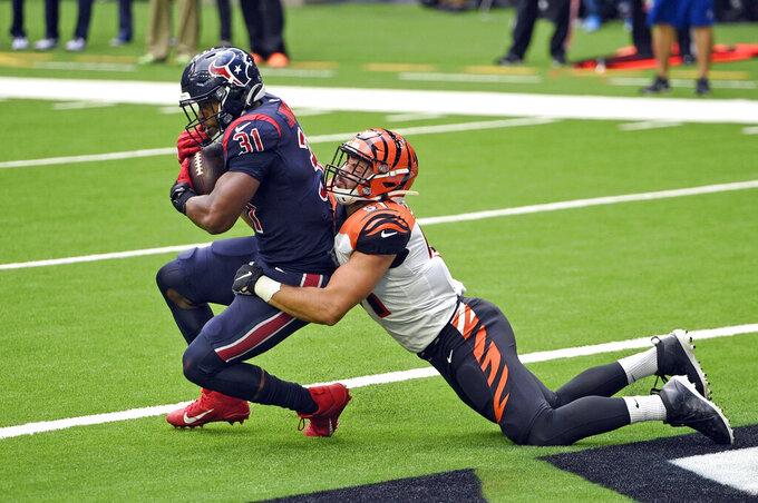 El running back David Johnson (31), de los Texans de Houston, atrapa un pase de touchdown ante el linebacker Markus Bailey, de los Bengals de Cincinnati, en el juego de NFL del domingo 27 de diciembre de 2020, en Houston. (AP Foto/Eric Christian Smith)