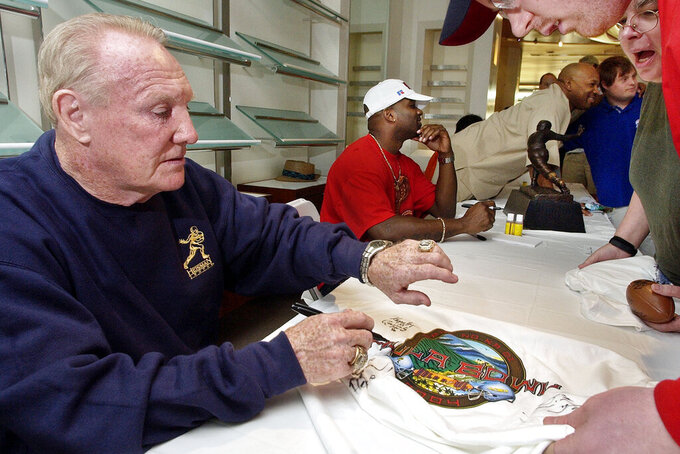 "FILE - In this Jan. 14, 2004, file photo, Howard ""Hopalong"" Cassady, Heisman Trophy winner from Ohio State in 1955, autographs a Hula Bowl T-shirt for a fan in Kaanapali, Hawaii. Cassady, a Heisman Trophy winner and former NFL running back, died early Friday, Sept. 20, 2019, in Tampa, Fla.,  Jerry Emig, the Ohio State associate athletic director said. He was 85. Cassady played both football and baseball at Ohio State in the early 1950s, winning the Heisman Trophy in 1955. He also played 10 seasons in the NFL, mostly with the Detroit, and got the nickname ""Hopalong"" from local sports writers after the black-hatted Western star of the 1950s. (AP Photo/Reed Saxon, File)"