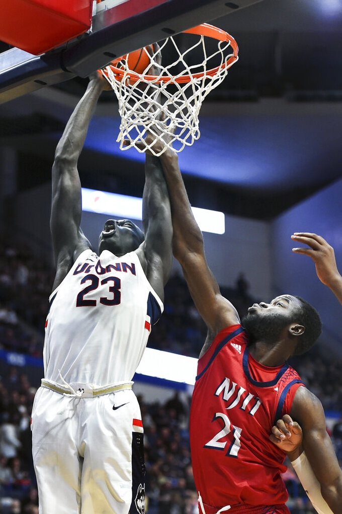 Connecticut's Akok Akok (23) shoots against New Jersey Institute of Technology's Souleymane Diakite (21) in the first half of an NCAA college basketball game Sunday, Dec. 29, 2019, in Hartford, Conn. (AP Photo/Stephen Dunn)