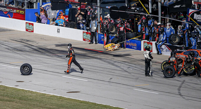 A pit crew member for Corey LaJoie chases a tire during a NASCAR Cup Series auto race at Texas Motor Speedway, Sunday, Nov. 3, 2019, in Fort Worth, Texas. (AP Photo/Brandon Wade)