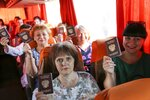 In this photo taken on Saturday, June 27, 2020, people show their Russian passports sitting on a a bus to Russia at a bus stop in Donetsk, eastern Ukraine. Residents of separatist-controlled regions in eastern Ukraine who have Russian citizenship are traveling to Russia to vote on constitutional amendments that would allow President Vladimir Putin to remain in power until 2036. Authorities of the self-proclaimed Luhansk and Donetsk People's Republics have organized bus services to polling stations in the neighboring Rostov region in Russia, in what is seen by many as part of the wide-spread effort to boost turnout at the controversial plebiscite. (AP Photo/Alexei Alexandrov)