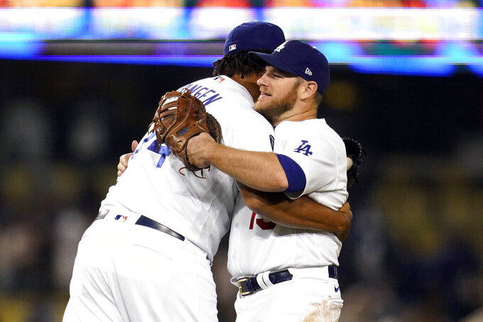 Los Angeles Dodgers relief pitcher Kenley Jansen, left, hugs Max Muncy after the Dodgers' 8-4 win over the Arizona Diamondbacks in a baseball game Tuesday, Sept. 14, 2021, in Los Angeles. (AP Photo/Marcio Jose Sanchez)