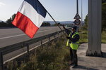 A protester holds a French flag and waves towards passing cars during a yellow vest demonstration at the l'Étoile road toll lanes marking the one year anniversary of the yellow vest movement near Marseille, southern France, Saturday, Nov. 17, 2019.  Some protests have clashed with police as yellow vest protesters are marking a year of protests, seeking what they see as economic justice for the French people with changes in government policies. (AP Photo/Daniel Cole)