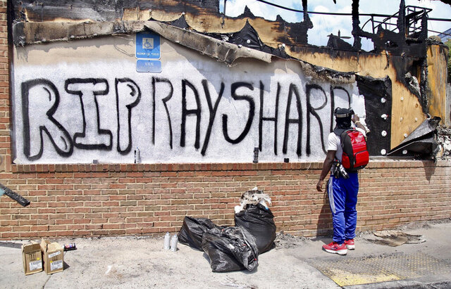 Joseth  Jett spray painted over the top of graffiti from the night before and paints RIP Rayshard Sunday, June 14, 2020, in Atlanta. On Saturday, protestors set fire to the Atlanta Wendy's where Rayshard Brooks, a 27-year-old black man, was shot and killed by Atlanta police Friday evening during a struggle in a Wendy's drive-thru line. (Steve Schaefer/Atlanta Journal-Constitution via AP)