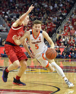 Virginia guard Kyle Guy (5) attempts to drive past the defense of Louisville guard Ryan McMahon (30) during the first half of an NCAA college basketball game in Louisville, Ky., Saturday, Feb. 23, 2019. (AP Photo/Timothy D. Easley)