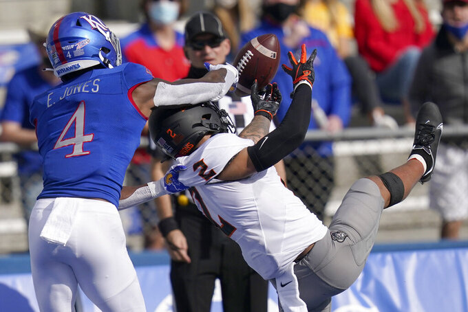 Kansas cornerback Elijah Jones (4) breaks up a pass intended for Oklahoma State wide receiver Tylan Wallace (2) during the first half of an NCAA college football game in Lawrence, Kan., Saturday, Oct. 3, 2020. (AP Photo/Orlin Wagner)
