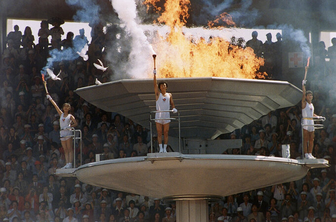 Pigeons fly around as the Olympic torch is lit during opening ceremonies in Seoul Sept. 17, 1988. (AP Photo/Michel Lipchitz)